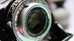 A modern circuit board is reflected in the lens of a 1950s Zeiss Ikon Nettar.