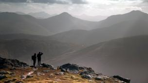 Walkers look out from the summit of Beinn Dorain