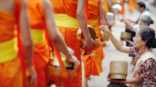 People offer food to Buddhist monks