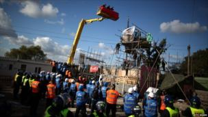 Police rise up in a cherry picker to talk to protestors stood on a scaffold platform during evictions from Dale Farm travellers camp on 19 October, 2011