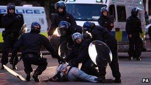 Police detain a man during rioting in Birmingham