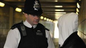A policeman talks to a youth in London