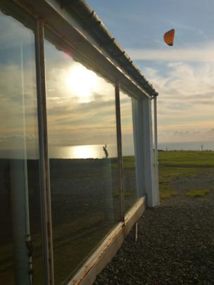 Reflection in a window of someone flying a kite near the sea