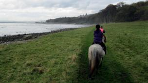 Riders on horseback with Dunrobin Castle in the background