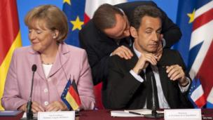 Silvio Berlusconi talks to French President Nicolas Sarkozy as German Chancellor Angela Merkel looks away in Paris, 4 October 2008