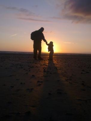 Man and child on beach