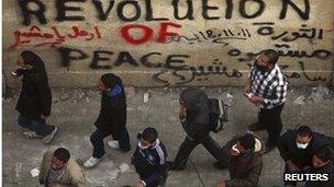 People walk past graffiti urging Tantawi to go (21 Nov 2011)