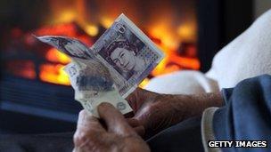 An elderly person holds cash facing a fire