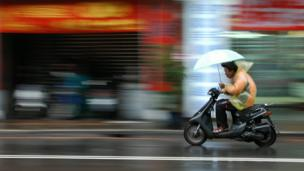 Man on a motor scooter with umbrella in the rain