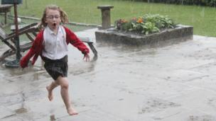A girl runs out of the rain