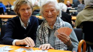 Christine Hess, left, plays cards with her mother Maria Hess in a school in Koblenz, Germany, on 4 December 2011