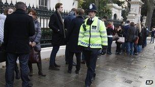 Expatriate Russians queue to vote in Russian Parliamentary elections watched by a British policeman outside their Embassy in London's Notting Hill on Sunday Dec 4
