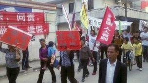 Residents holding placards march on a street during a protest in Wukan village of Lufeng, China's Guangdong province, 22 November 2011