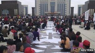 Residents sit next to a banner outside the city government building during a protest in Lufeng on 21 November