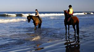 Women on horses on the seashore
