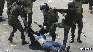 Egyptian army soldiers arrest a female protester during clashes at Tahrir Square in Cairo December 17, 2011