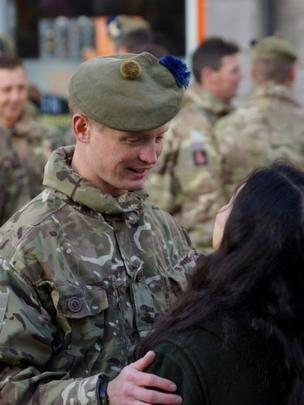Soldier and a woman greet each other