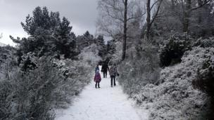 A family walk along a snow covered path