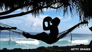 Man drinks coconut milk sat on a hammock