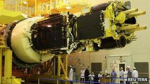 Engineers prepare a geostationary communications satellite at Baikonur Cosmodrome