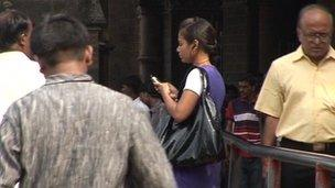 An Indian lady uses her mobile phone in the street