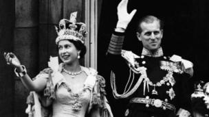 Queen Elizabeth II and her husband Prince Phillip waving to crowds from the balcony of Buckingham Palace.