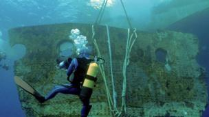 Diver looking at piece of ship's body under water.