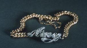 Bracelet with name carved name Amy attached to it.