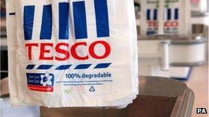 Tesco carrier bags hanging at a checkout