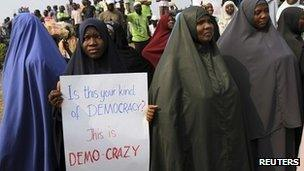 Muslim women holding placards asking what kind of democracy is this?