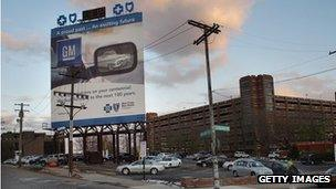 An advertisement for General Motors is displayed near the company's headquarters in Detroit, Michigan