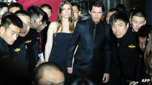 Christian Bale and his wife Sibu are escorted by Chinese security guards at the Flowers of War premiere in Beijing, December 12 2011