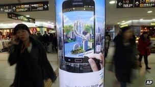 People walk by a billboard of Samsung Electronics Galaxy Note at a subway station in Seoul, South Korea, on 6 January, 2012