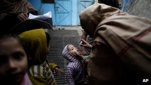 A child is administered polio drops by health workers at his residence during a door to door drive in Delhi