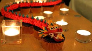 Chinese dragon made of icing resting on cupcakes