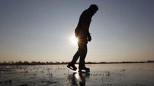 A man ice skates on the frozen fens in Welney, Norfolk