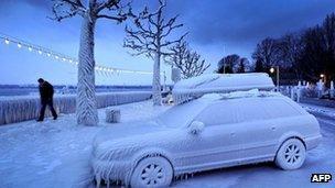 A man walks past an ice covered car on the frozen waterside promenade at Lake Geneva, Switzerland