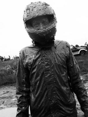 A man in a motorbike helmet covered in mud