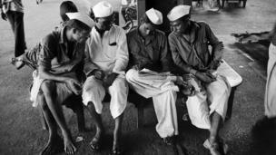 Railway porters reading a newspaper (Photo: Pablo Bartholomew)