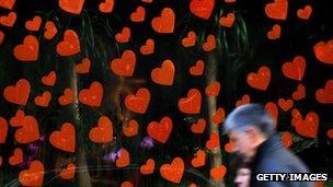 A man walks past a lot of hearts