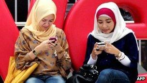 Two women use social media on their mobiles in Jakarta on 11 February 2012