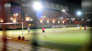 A game of football with Rangers football club in the background