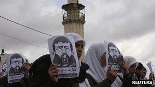 Students hold pictures of Palestinian hunger striker Khader Adnan in Nablus, the West Bank, 19 February
