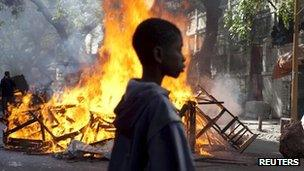 """A boy stands in front of a burning barricade set up by anti-government protestors during clashes with police in Senegal""""s capital Dakar, February 19, 2012."""