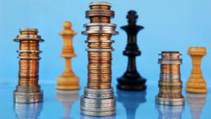 Money and chess pieces