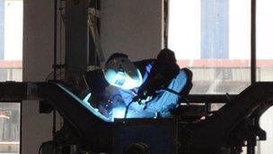 Worker welding railway bogie at Bombardier Transportation factory in Savli