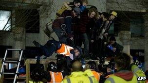 A bailiff is pulled from a makeshift barricade at the Occupy protest camp