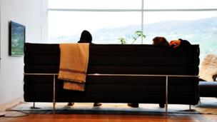 People relaxing on a sofa