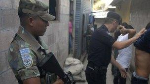 Soldier stands guard as police look for drugs and weapons in San Salvador, El Salvador's capital in January 2012