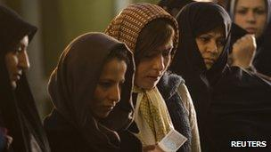 Women wait in line to vote for the parliamentary election in a mosque in south Tehran
